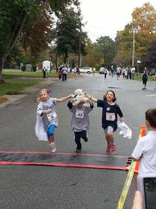 Baby was Kayla's favorite stuffed animal and by her side all times. Here, Baby epitomizes Kayla's spirit by crossing the finish line at the Kisses 4 Kayla 2013 5K with Kayla's sister Ava and friends